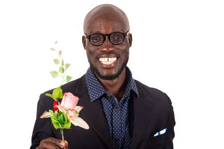 Photo pour handsome smiling young man wearing black jacket and glasses holding a bouquet of flowers; preparing for a date with his girlfriend. Valentine's Day. Mothers' Day - image libre de droit
