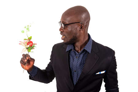 Photo pour handsome smiling young man wearing black jacket and glasses standing sideways and holding a bouquet of flowers; get ready for an appointment with his girlfriend. Valentine's Day. Mothers' Day - image libre de droit