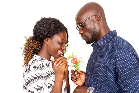Photo pour young man standing on white background offering a flower to his girlfriend while this one has her eyes closed smiling - image libre de droit
