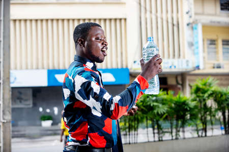 Photo pour handsome young businessman standing in shirt and holding and drinking mineral water in a plastic bottle on the street while smiling - image libre de droit