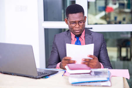 Photo pour concentrated adult businessman sitting in front of laptop and reading report on paper in office. - image libre de droit