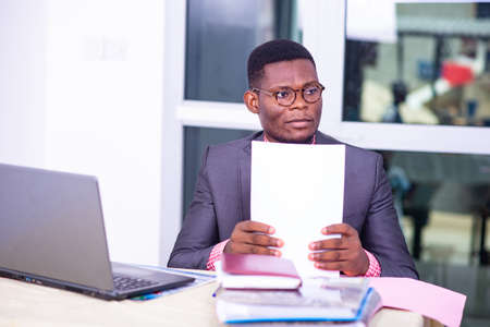 Photo pour Serious adult businessman sitting in front of laptop and holding paper report in office. - image libre de droit
