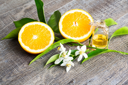 Photo for Juicy Orange cut in two parts and neroli, flowers  of orange tree, on rustic wood background. The Orange blossom is the fragrant flower of the Citrus is used in perfume and tea, aphrodisiac. - Royalty Free Image