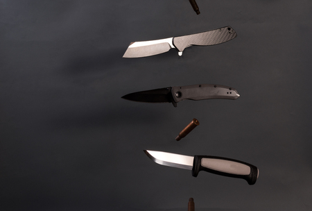 Three different knives in the air. Knives fly in different directions. Falling sleeves.