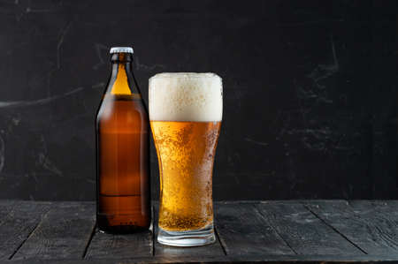 Photo pour Beer bottle and glass with beer and foam. Dark bottle of beer. Low key. - image libre de droit