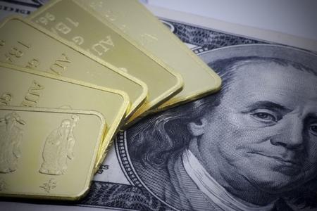 Gold bar ingot close up on the US money dollar background