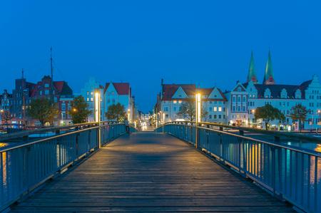 Photo pour Historical cityscape with pedestrian bridge on the river Trave in Lubeck at the Baltic Sea - image libre de droit