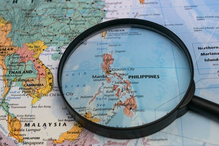 Photo pour Map of the Philippines through magnifying glass on a world map. - image libre de droit