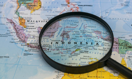 Photo pour Map of Indonesia through magnifying glass on a world map. - image libre de droit