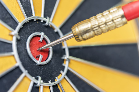 closeup dart arrow hitting in target bullseye of dartboard, business data integration solutions and success concept