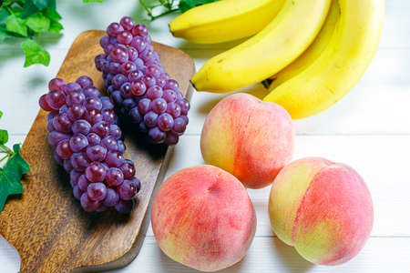 Photo for Fresh peaches, grapes and bananas on wooden table - Royalty Free Image