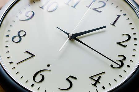 Foto de Close up of a clock isolated on wooden table - Imagen libre de derechos