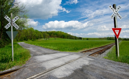 Country Railroad Crossing:  A narrow gravel road crosses a set of railroad tracks in rural Virginia.