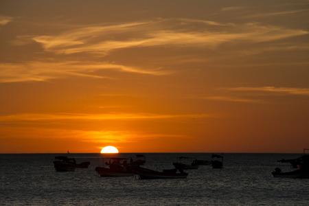 Sunset over the sea with boats in the background in the bay of San Juan del Sur in Nicaragua