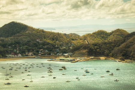 View over the beautiful bay of San Juan del Sur in Nicaragua with boats on the water and mountains in the background