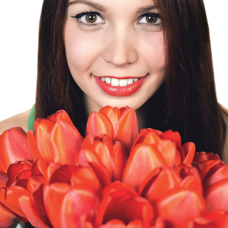Beautiful and attractive young adult girl with the bouquet of red tulips flowers isolated on a white background.