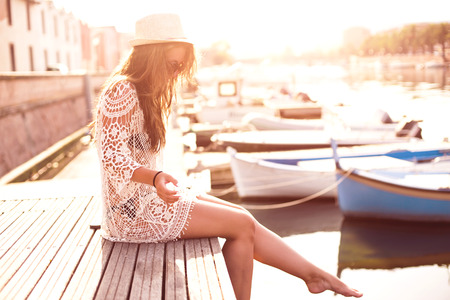 Young woman in hat and cute summer dress standing on the pier with peaceful town scenery, looking at sunset.