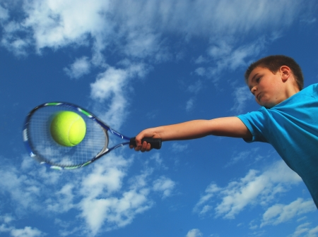 tennis. A little boy hitting a forehand shot with racket
