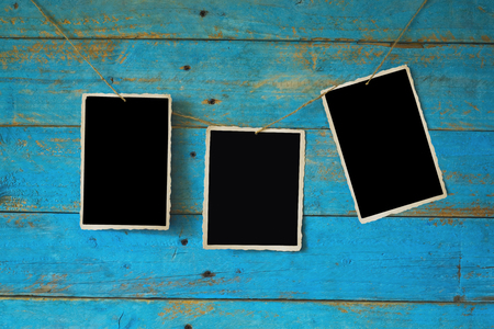 Empty photo frames hanging on old blue grungy wooden planks background