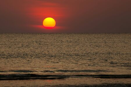 Photo for Big sun setting down over the sea, The red disc of the sun touches the horizon in the ocean. - Royalty Free Image