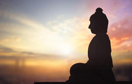 Photo pour Silhouette of Buddha statue against sunset background - image libre de droit