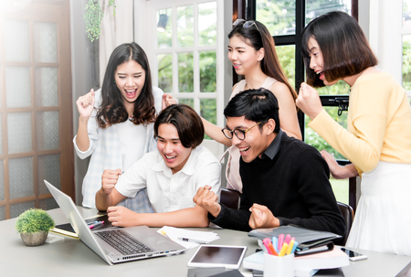 Foto de group of young asian student discussing about interesting things in laptop at coworking space. - Imagen libre de derechos