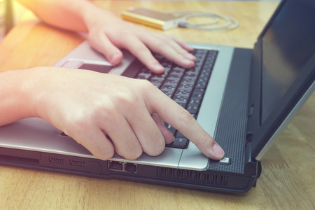 Turn on the switch laptop on desk,closeup man using notebook on wooden table