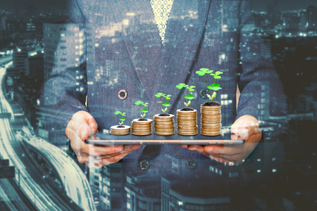 Foto de Businessman holding a tablet with coins stack and tree,Lucky economic growth concept - Imagen libre de derechos