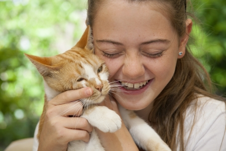 young girl holding her ginger cat