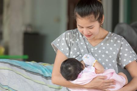 Foto de Beautiful happy mother breastfeeding her baby. - Imagen libre de derechos