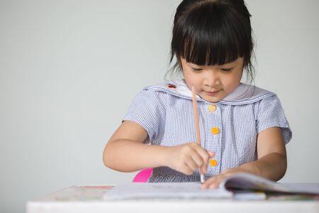 Photo pour Little asian kid doing homework at home. - image libre de droit