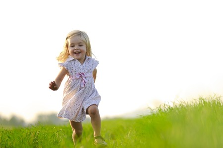 Photo for Young girl runs through a field, happy and having fun. - Royalty Free Image
