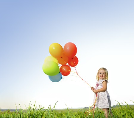 Foto de Adorable young girl holds tightly to a large bunch of helium filled balloons - Imagen libre de derechos