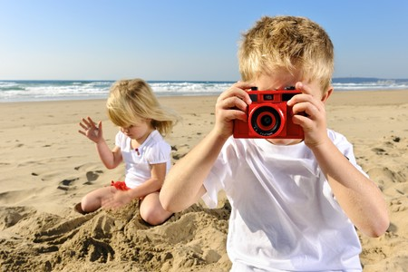 Young boy takes a picture at the beach with his red camera