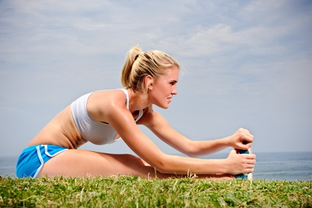 Young blond female stretches her leg on the grass