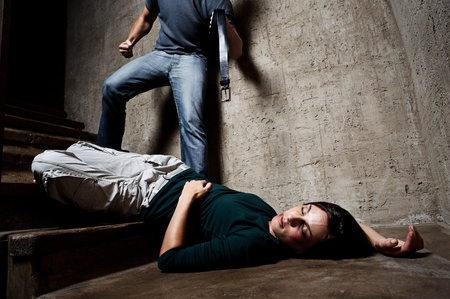 Battered woman lies lifelessly at the bottom of stairs with a faceless man holding a belt, a conceptual shoot portraying the process and effects of domestic violence