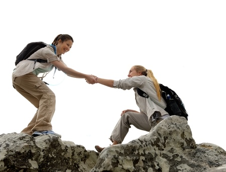 Foto de Hiker woman helps her friend climb up the last section of mountain. teamwork in outdoor lifestyle adventure - Imagen libre de derechos