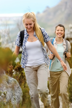 two young woman go hiking outdoors and smile as they walk