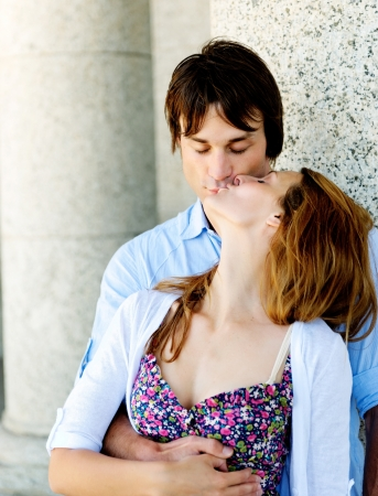 Real couple have a real kiss while leaning against a pillar