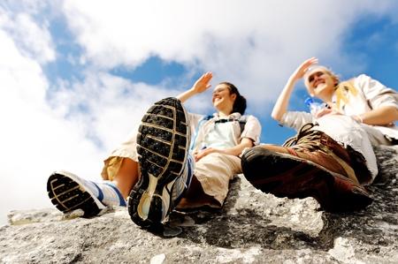 Foto de two women take a break from trekking and rest on a rock outdoors - Imagen libre de derechos