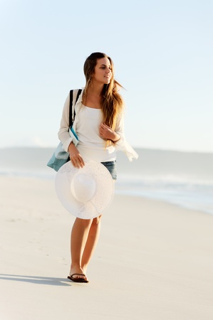 girl walking along the shoreline with beach hat and bag