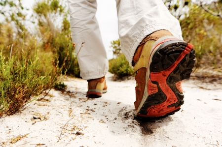 person hiking outdoors, boot on sandly pathway in the wilderness. trekking