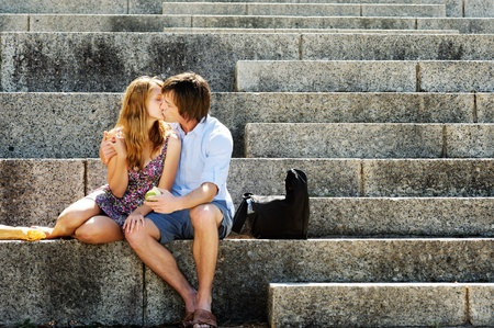 A couple traveling sit on the steps of a local landmark and kiss in the afternoon sunlight