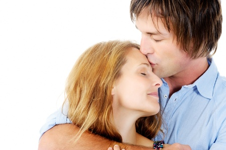 Handsome man kisses loving girlfriend on her forehead, isolated on white