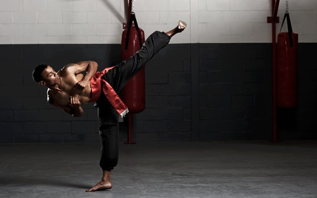 Kung fu student practises his kicks in the gym, training for a fight