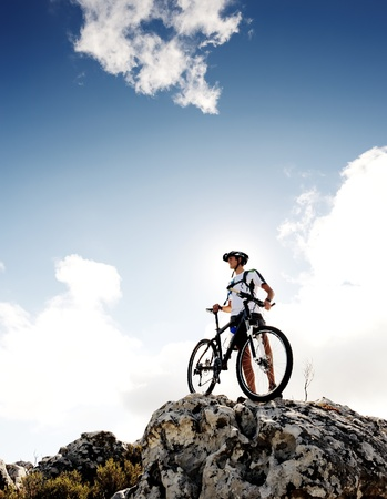 confident mountainbike rider standing and observing the view