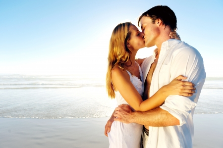 Photo pour Newlywed couple kissing on honeymoon, beach vacation in summer and an intimate moment. - image libre de droit