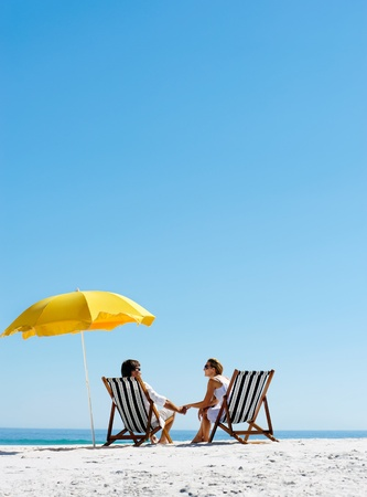 Foto de Beach summer couple on island vacation holiday relax in the sun on their deck chairs under a yellow umbrella. Idyllic travel background. - Imagen libre de derechos