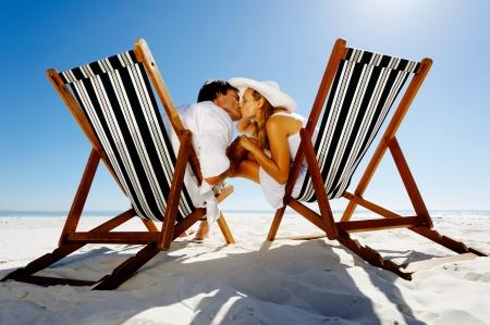 Foto de Summer beach kissing couple sitting on deck chairs enjoying an intimate moment - Imagen libre de derechos