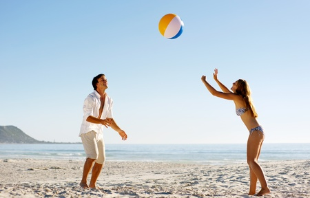 Photo pour Young couple on a summer beach vacation playing with a beachball and having carefree fun - image libre de droit